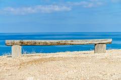 由海的手工制造长木凳 免版税库存图片