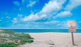 在海滩的木标志在撒丁岛 免版税库存照片