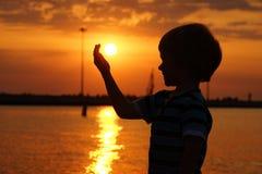 由海的男孩日落的 免版税库存照片