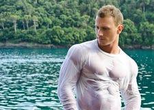 由海的英俊的年轻爱好健美者有湿衬衣的 免版税图库摄影