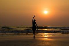 由海的跳芭蕾舞者的剪影日落光的在Arambol 免版税图库摄影