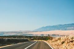 由海的风景路在导致Pag的克罗地亚,在海岛上,有山的在背景中 库存照片