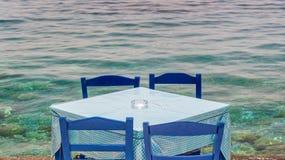 由海的餐馆桌在克利特希腊村庄  图库摄影