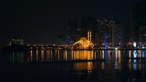 由海盐水湖的小船浮游物在清真寺前面照亮与金光 大城市夜视图  在megapolis的海滨 影视素材