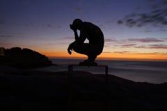 由海蹲下的人的雕塑 库存照片