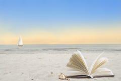 由海运开张在海滩的书 免版税图库摄影