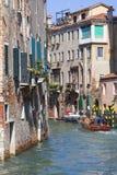 由游人的城市游览有汽艇的,旁边狭窄的渠道,威尼斯,意大利 免版税库存图片