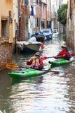 由游人的城市游览有皮船的,狭窄的渠道,威尼斯,意大利 免版税库存照片