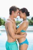 由游泳池的浪漫夫妇在一个晴天 免版税库存图片