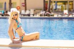 由游泳池的逗人喜爱的白肤金发的妇女 免版税库存图片