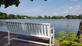 由湖的白色长凳 免版税库存图片