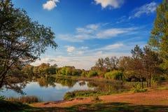 由湖的美丽的景色在日落期间在一个夏天晚上 庄严美丽如画的天空从寂静的水反射 免版税库存照片
