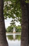 由湖的老木管乐器类磨房构筑与两个树干 免版税库存照片