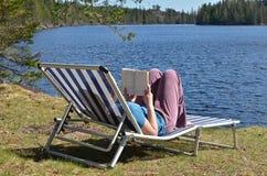 由湖的阅读书 免版税库存照片