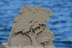 由湖的Sandsculpture树 免版税图库摄影