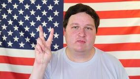 由满意的肥胖人的和平和爱标志美国旗子的背景的 股票录像