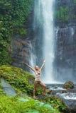由瀑布的少妇实践的瑜伽 免版税库存图片