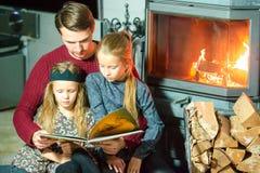 由火地方生和他的两个小孩阅读书和放松某一冷的晚上onChristmas前夕 图库摄影