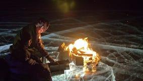 由火的三个旅客在冰在晚上 在冰的营地 帐篷在火旁边站立 贝加尔湖湖 附近 影视素材