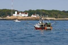 由灯塔的渔拖网渔船 库存图片