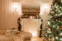 由烛光的圣诞节晚上 与一个白色壁炉,装饰的树,明亮的沙发,大窗口的经典公寓 免版税库存照片