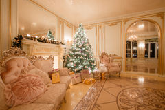 由烛光的圣诞节晚上 与一个白色壁炉,装饰的树,明亮的沙发,大窗口的经典公寓 库存图片