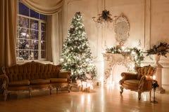 由烛光的圣诞节晚上 与一棵白色壁炉,装饰的树,沙发,大窗口的经典公寓和 免版税库存图片