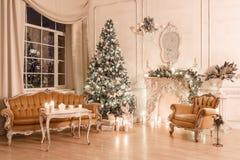 由烛光的圣诞节晚上 与一棵白色壁炉,装饰的树,沙发,大窗口的经典公寓和 图库摄影