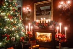 由烛光的圣诞节晚上 与一棵白色壁炉,装饰的树,沙发,大窗口的经典公寓和 免版税图库摄影