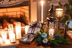 由烛光的圣诞节晚上 与一棵白色壁炉,装饰的树,沙发,大窗口的经典公寓和 免版税库存照片