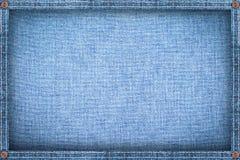 由牛仔布做的框架,蓝色牛仔裤背景 免版税库存照片