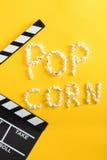 由玉米花和电影拍板做的玉米花字法在黄色 免版税库存图片