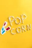由玉米花和3D玻璃做的玉米花字法在黄色 免版税库存照片