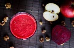由甜菜根、红萝卜、苹果和核桃做的新鲜的未加工的素食红色圆滑的人在黑暗,木背景,顶上的看法 免版税库存图片