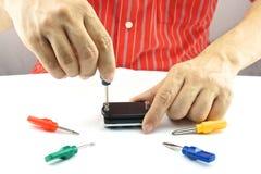 由用途五颜六色的螺丝刀的人修理 免版税图库摄影