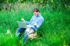 户外年轻人与杯子和膝上型计算机 库存照片