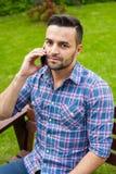 由电话供以人员坐长凳在庭院里和谈话 免版税图库摄影