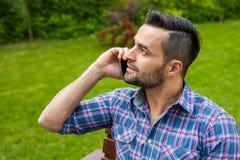 由电话供以人员坐长凳在庭院里和谈话 免版税库存照片