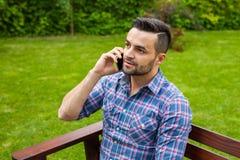 由电话供以人员坐长凳在庭院里和谈话 免版税库存图片