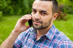 由电话供以人员坐长凳在庭院里和谈话 图库摄影