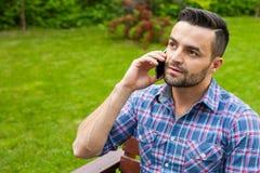由电话供以人员坐长凳在庭院里和谈话 库存图片
