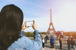 由电话的妇女旅游采取的照片在埃佛尔铁塔附近在阳光和蓝天下的巴黎 著名普遍旅游 免版税库存图片
