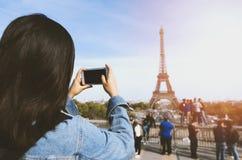 由电话的妇女旅游采取的照片在埃佛尔铁塔附近在阳光和蓝天下的巴黎 著名普遍旅游 免版税库存照片
