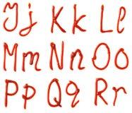 由番茄酱糖浆做的字母表信件 库存图片