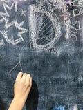 由白垩的儿童油漆在校务委员会 免版税库存照片