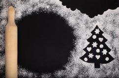 由白色小麦面粉、圣诞树和一根滚针做的酥皮点心的一张典雅的图片 免版税库存照片