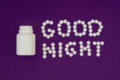 由白色药片做的题字晚安 在紫罗兰色背景的药瓶 失眠概念 库存图片