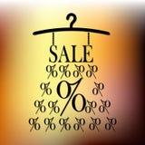 由百分之做的销售礼服在挂衣架在金背景 免版税图库摄影