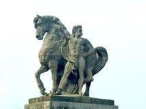 由的马和附近站立一个的人的雕塑 免版税库存图片