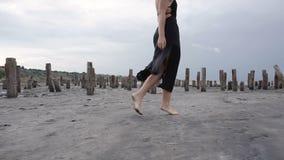 由盐峡湾海岸的可爱的苗条白肤金发的步行有健康黑泥的 股票视频